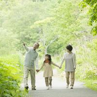 新緑の中で手をつなぐ祖父母と孫