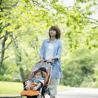赤ちゃんの乗るベビーカーを押す母親