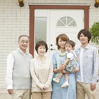 玄関前で微笑む3世代家族