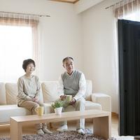 ソファに座りテレビを見るシニア夫婦