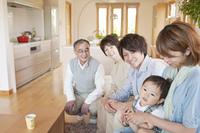 ソファに座り微笑む3世代家族