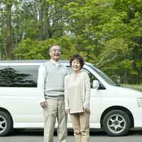 車の前で微笑むシニア夫婦