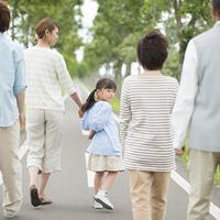 一本道を歩く3世代家族の後姿