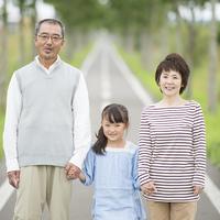 手をつなぎ微笑む祖父母と孫