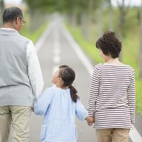 手をつなぐ祖父母と孫の後姿