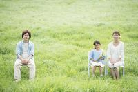 草原で椅子に座り微笑む親子
