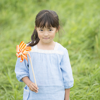 草原で風車を持ち微笑む女の子