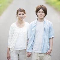 一本道で手をつなぎ微笑むカップル