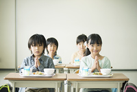 給食を前に手を合わせる小学生