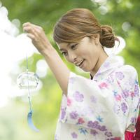 風鈴を持ち微笑む浴衣姿の女性