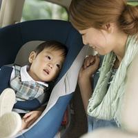 チャイルドシートに乗る子供と会話をする母親