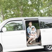 車の中で子供を抱き微笑む母親