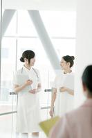 病院ロビーを歩く看護師