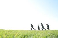 草原を走るビジネスマンとビジネスウーマン