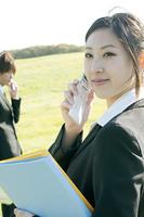 草原で携帯電話を持ち微笑むビジネスウーマン
