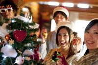 クリスマスツリーの周りで微笑む若者たち