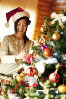 クリスマスツリーの飾り付けをする女性