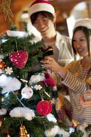 クリスマスツリーの飾り付けをする若者たち