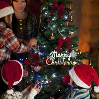 クリスマスツリーに飾り付けをする子供たちと母親