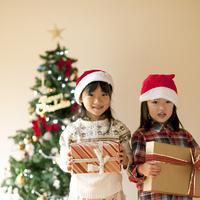 クリスマスツリーの前でプレゼントを持つ子供たち