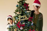 クリスマスツリーの後ろで微笑む親子