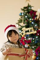 クリスマスプレゼントを持ち微笑む女の子