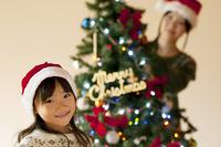 クリスマスツリーの前で微笑む女の子