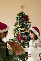 母親からクリスマスプレゼントを受け取る女の子