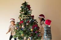 クリスマスツリーの周りを歩く子供たち