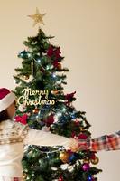 クリスマスツリーの前で手をつなぐ子供たち