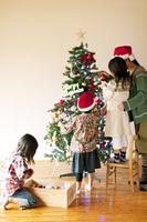 クリスマスツリーの飾り付けをする子供たちと母親