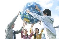 地球のボールを持つ若者たち