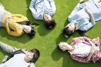 芝生の上で眠る若者たち