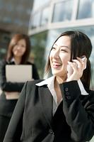 携帯電話で話をするビジネスウーマン