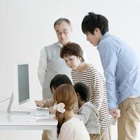 パソコンを使う子供たちを見守る家族