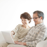 パソコンの画面を見るシニア夫婦