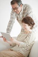 タブレットPCの画面を見るシニア夫婦