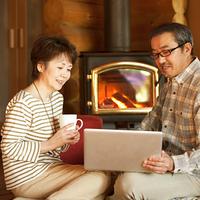 暖炉の前でパソコンをするシニア夫婦