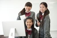 パソコンの周りで微笑む中学生
