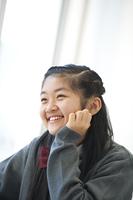 頬杖をつき微笑む中学生