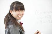 ホワイトボードの前で微笑む中学生