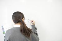 ホワイトボードに数式を書く中学生の後姿