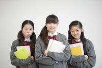 勉強道具を持ち微笑む中学生
