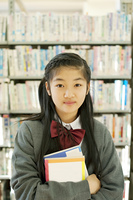 本棚の前に立つ中学生