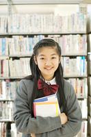 本棚の前で微笑む中学生
