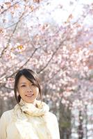 桜の前で微笑む女性