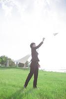 紙飛行機を飛ばすビジネスマン