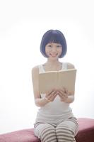 ソファで本を持つ笑顔の女性