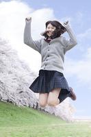 桜の木の前でジャンプする女子高生