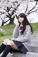 桜の木の下で座る女子高生